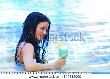 Beautiful woman in swimming pool with cocktail - stock photo