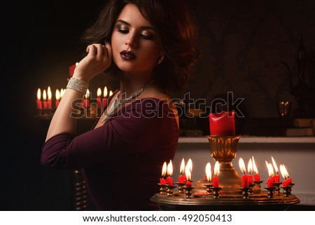 Beautiful woman in the dark room with a lot of candles
