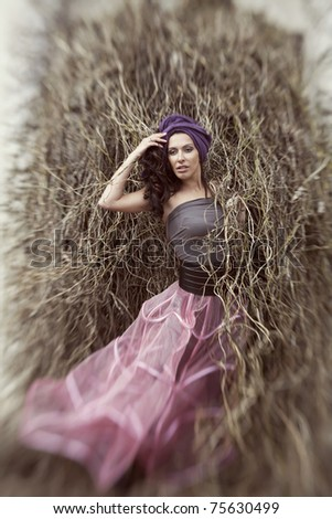 beautiful woman in the fashion pink skirt and a turban in the park - stock photo