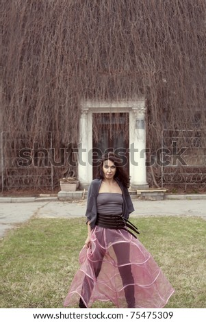 beautiful woman in the fashion pink skirt  in the park - stock photo
