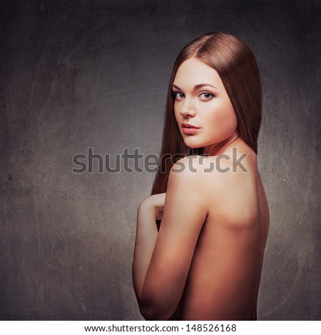 beautiful woman in the fog with naked back portrait over dark background, looking at camera - stock photo