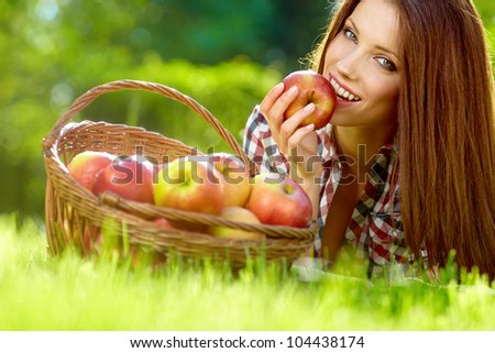 Beautiful woman in the garden with apples - stock photo