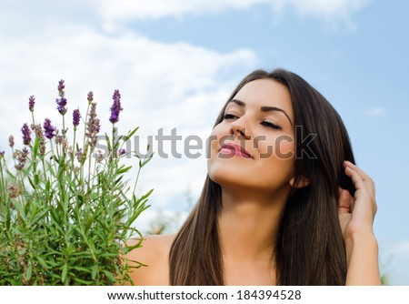 Beautiful woman in the garden with flowers. Girl relaxing near a bouquet of lavender on a hot summer day, enjoying the nature. - stock photo