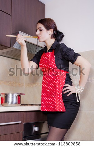Beautiful woman in the kitchen interior cooking - stock photo