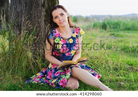 Beautiful woman in the Park sitting on the grass near the big tree and reading a book on a summer evening - stock photo