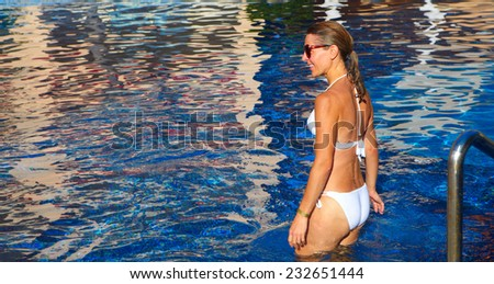 Beautiful woman in the pool. Relaxation at tropical resort      - stock photo