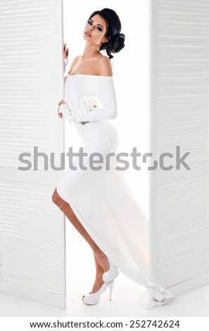 Beautiful woman in the white dress next door - stock photo