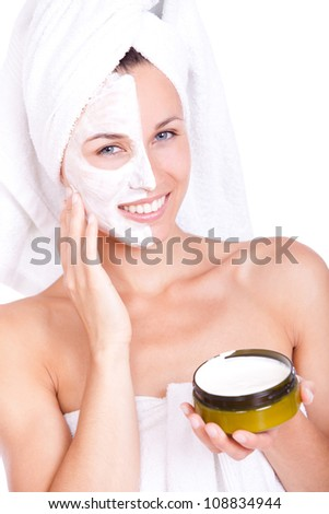 Beautiful woman in towel with facial mask over white background - stock photo