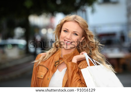 Beautiful woman in town holding shopping bags - stock photo