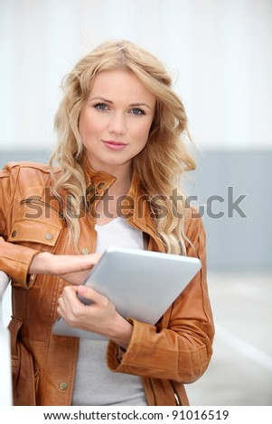 Beautiful woman in town using electronic tablet - stock photo