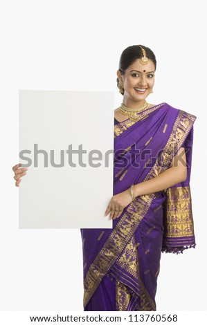 Beautiful woman in traditional Assamese dress holding a blank placard and smiling - stock photo