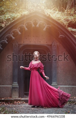 Beautiful woman in vintage burgundy dress with flying train on a background of a Gothic arch.