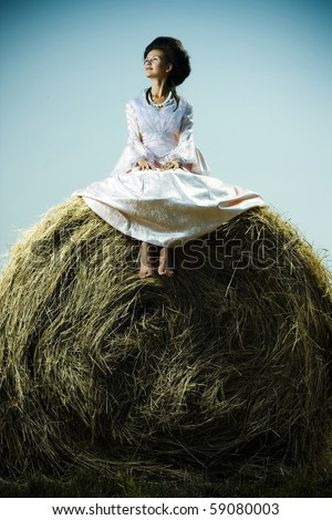 Beautiful woman in vintage dress sitting on haystack - stock photo