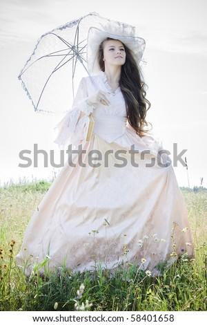 Beautiful woman in vintage dress walking across a field - stock photo