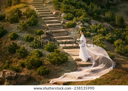 Beautiful woman in vintage wedding dress stay on stairs among mountain landscape and  holding white bouquet - stock photo