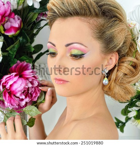 Beautiful woman in violet gown dress. White Luxury studio with flowers. - stock photo