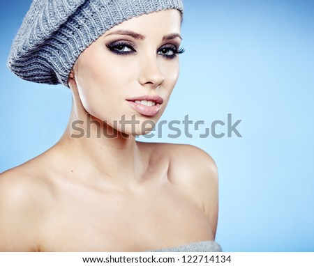 beautiful woman in warm clothing on blue background - stock photo