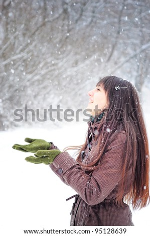 Beautiful woman in warm clothing with snow, catching snowflakes
