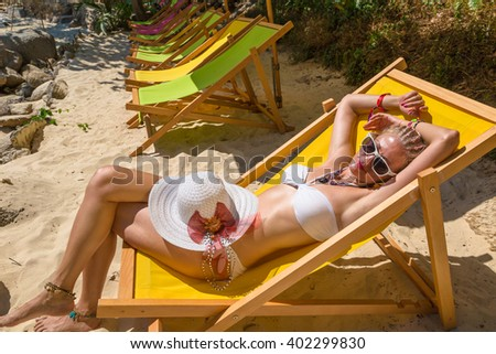 Beautiful  woman in white bikini, sunglasses and hat sunbathing on a deck chair on Paradise Beach, the most glamorous beach of Patong, Phuket in Thailand. - stock photo