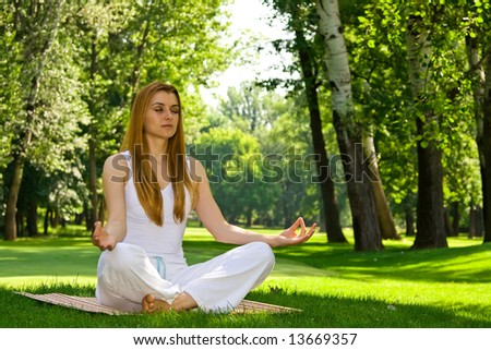 Beautiful woman in white doing yoga outdoors.