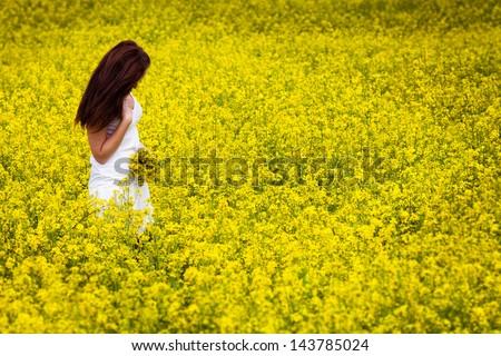 Beautiful Woman in white dress holding a bunch of rape flowers. Rape Field. Yellow Field. rapeseed plantation. Canola Field. Girl In Field. - stock photo