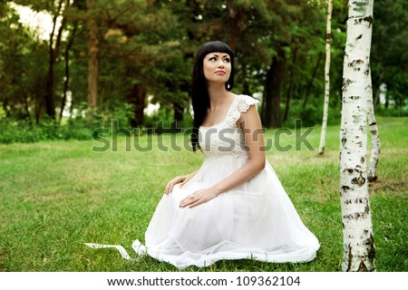 Beautiful woman in white dress outdoors in summer - stock photo