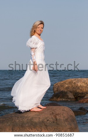 Beautiful woman in white dress standing on the rock and posing - stock photo