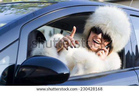 Beautiful woman in white fur coat speaking on the phone in car