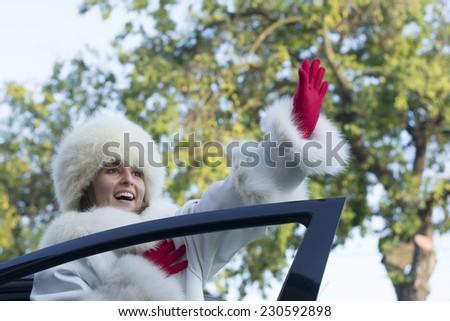 Beautiful woman in white fur coat waving from an open car door - stock photo