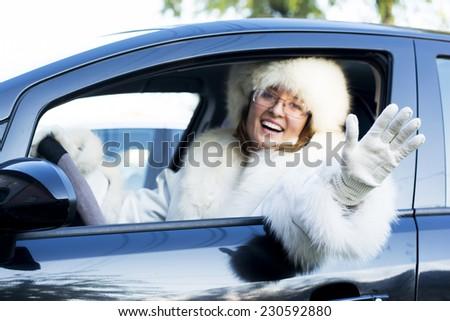 Beautiful woman in white fur coat waving from an open car window - stock photo
