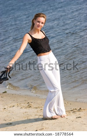 Beautiful woman in white slacks running on sea shore holding shoes