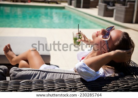 Beautiful woman in white summer dress laying with mojito cocktail on lounge chair at poolside. Luxury vacation - stock photo