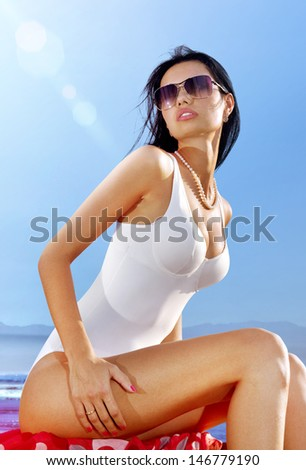 beautiful woman in white swimming suit sits on coast and takes sun bath - stock photo