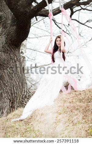 Beautiful woman in white wedding dress shaking on a swing - stock photo