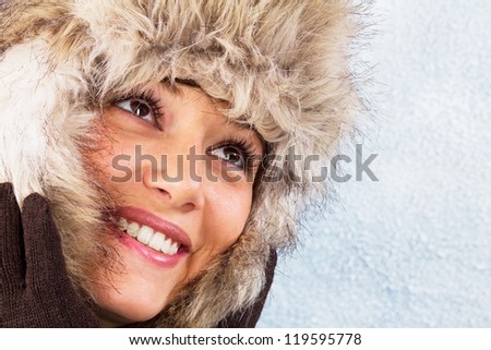 Beautiful woman in winter clothes with a bright smile. Studio shot against a light blue background as a wintry close up portrait with copy space - stock photo