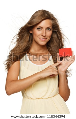 Beautiful woman in yellow dress holding empty credit card and pointing at it,  isolated on white background - stock photo