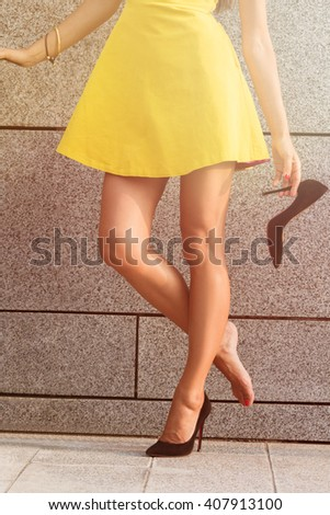 Beautiful woman in yellow dress holding one heel in her hand. Woman's legs in full length. Girl put off one heel to have a rest. Toned image. - stock photo
