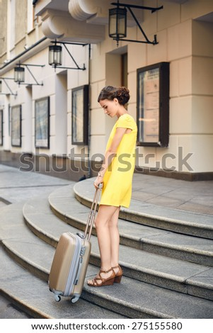 Beautiful woman in yellow dress with the suitcase at the entrance to the hotel - stock photo