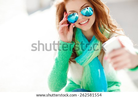 Beautiful woman, instagram. woman taking a selfie with smart phone outdoors in the city on sunny summer day. Closeup shot. Cute teenage girl with red hair posing for self portrait - stock photo