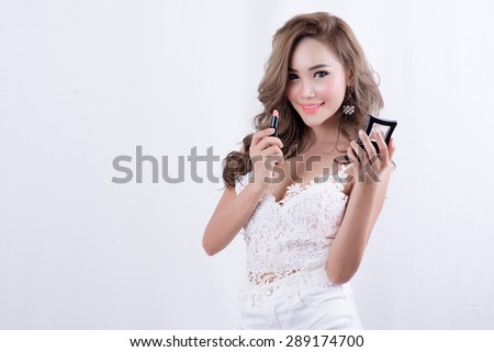 beautiful woman is applying her lips with pink lipstick,Woman with lipstick - stock photo