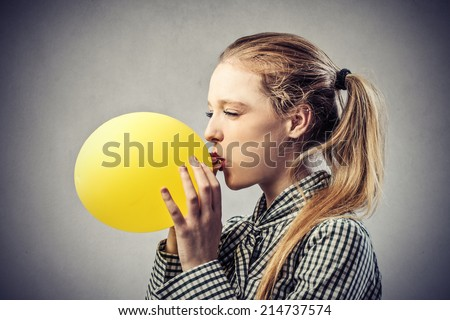 beautiful woman is blowing up a yellow balloon - stock photo