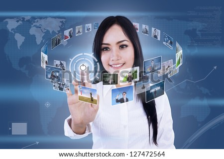 Beautiful woman is clicking on touch screen to choose digital photos - stock photo