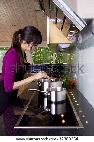 Beautiful woman is cooking in a modern home