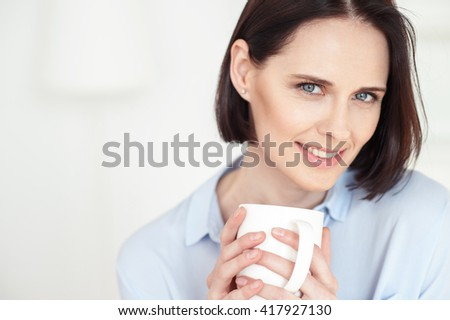 Beautiful woman is drinking adorable beverage - stock photo