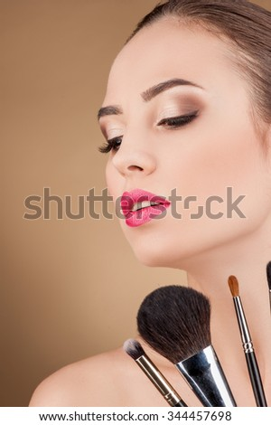 Beautiful woman is getting make-up. She is looking down with passion. There variation on make-up brush near her face - stock photo