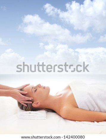 Beautiful woman is getting spa treatment over the sea and sky background - stock photo