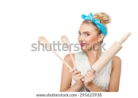 Beautiful woman is holding wooden spoons and rolling pin in her hands. She is smiling and looking towards with anticipation. Isolated on background and copy space in left side - stock photo