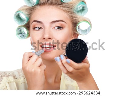 Beautiful woman is painting her lips with lipstick. She is holding mirror and looking at it with attention. The lady has curlers on her hair. Isolated on background and copy space in right side - stock photo