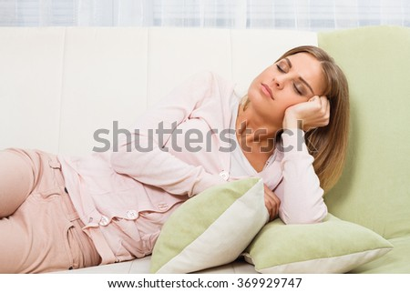 Beautiful woman is resting at sofa.Woman napping