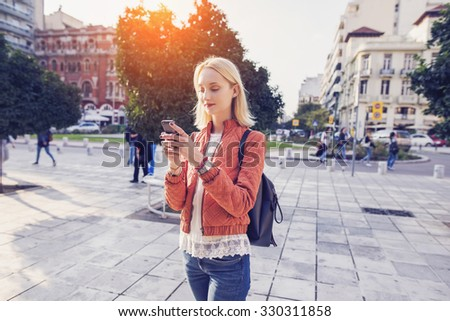 beautiful woman is sending a text message using an app on her smartphone while walking in the street on a sunset background - stock photo